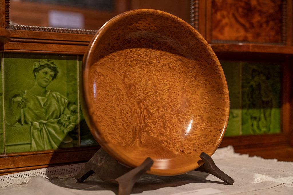 Eine Schale aus Kauri Holz ausgestellt auf einer Komode, die mit gruenen Kacheln dekoriert ist,im Kauri Museum von Matakohe