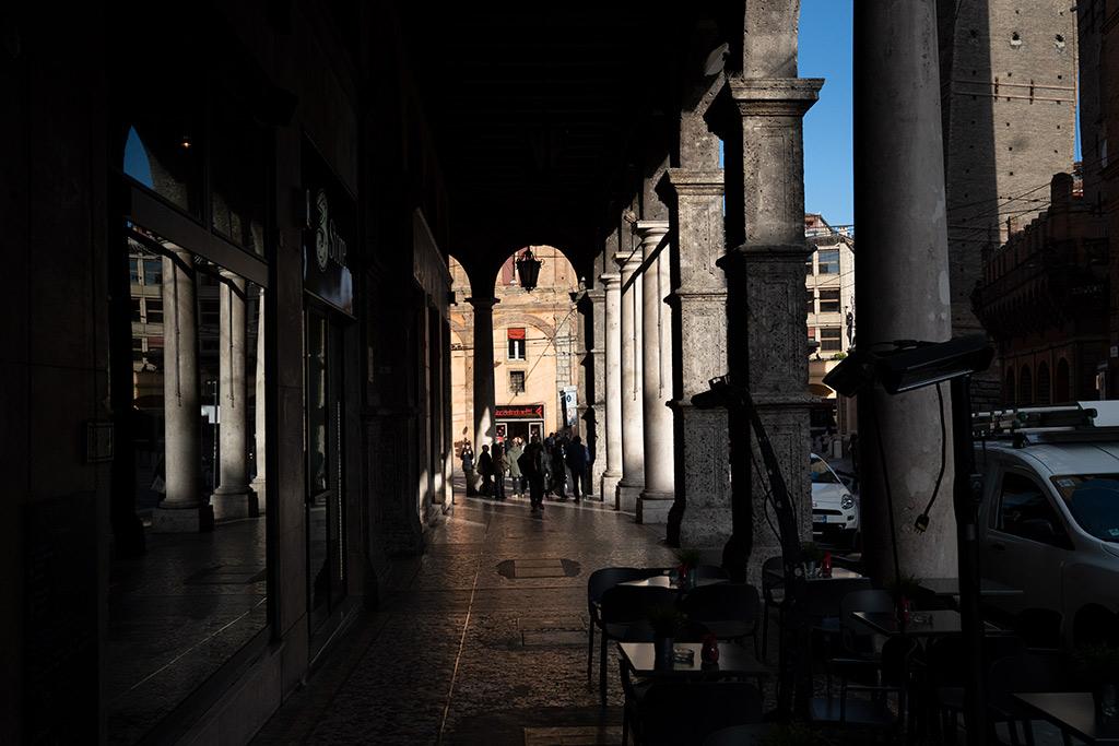 Verschatteter Arkadengang in Bologna. Im Hintergrund blauer Himmel.
