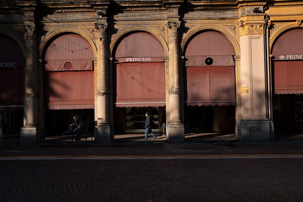 Vier Bögen einer Arkade sind von Sonne beschienen. Unter der Arkade läuft ein Mann. Auf der Straße fährt eine Frau mit einem Fahrrad vorbei.