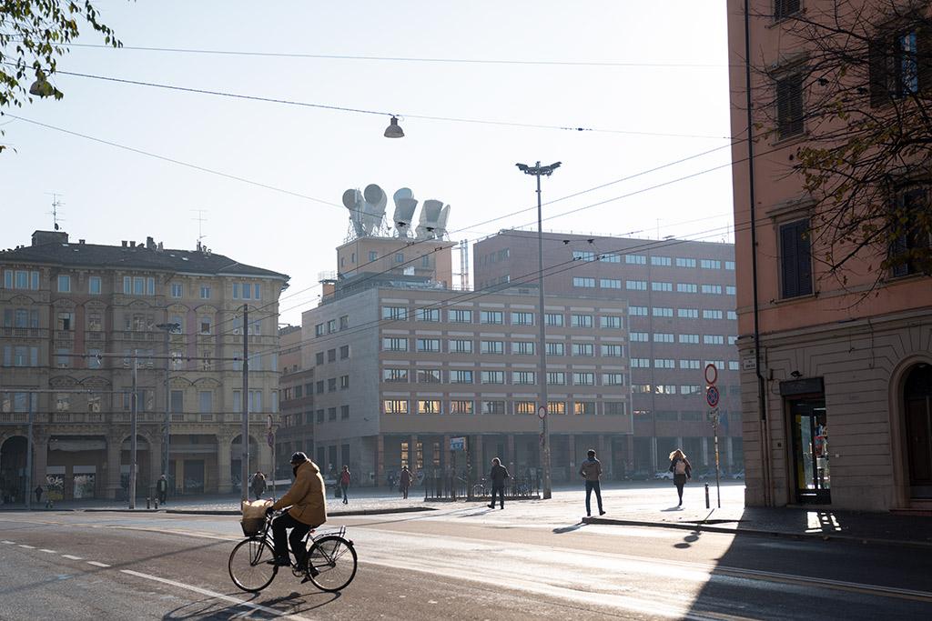 Eine Kreuzung in Bologna dahinter ein großer Platz. In den Fenstern der modernen Gebäude spiegelt sich die Morgensonne.