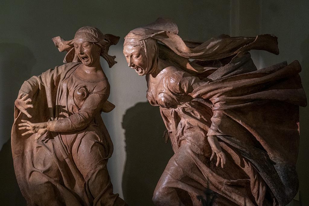 Zwei Frauenfiguren aus Terrakotta. Die Eine stürzt mit einem bewegten Gewand nach vorne. Die andere hat die Hände abwehrend erhoben. Beide haben die Münder weit aufgerissen, als ob sie schreien wollten.