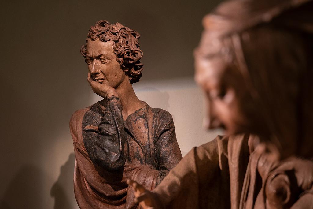 Ein junger Mann hält sich die rechte Hand unter das Kinn. Er hat lockige Haare. Sein Gesicht zeigt den Ausdruck von tiefer Trauer.