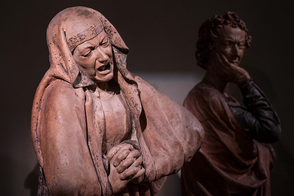 Eine alte Frau mit schmerzverzehrten Gesicht. Die Haare sind von einem Schleier umgeben. Die Hände sind wie zum Gebet gefaltet.