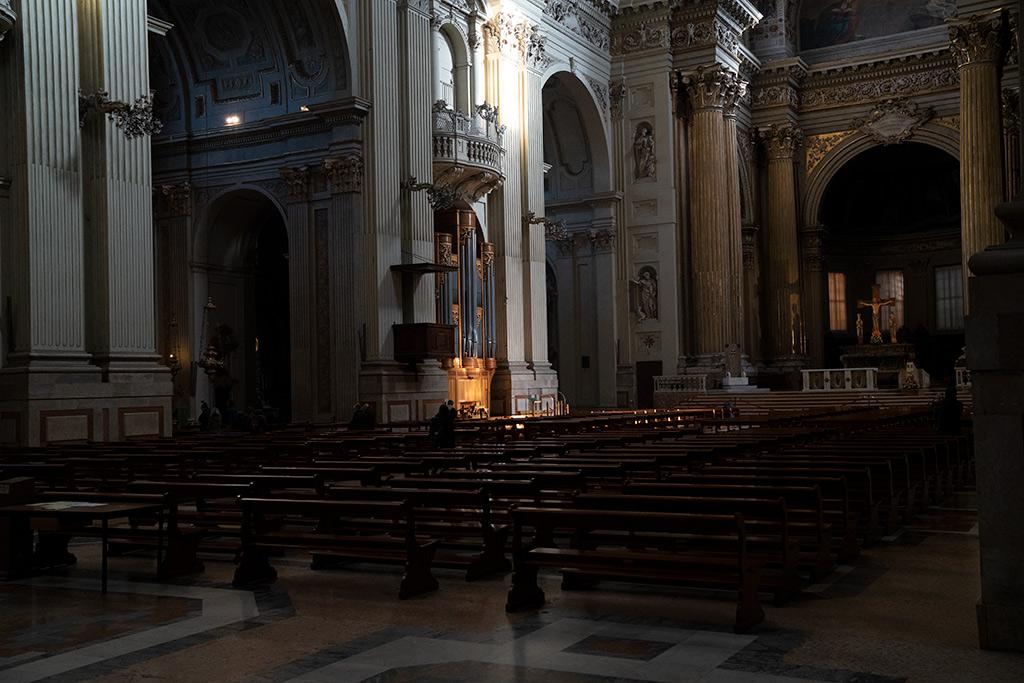 Das Kirchenschiff der Doms von Bologna. Vergoldete Säulen schmücken große weiße Pfeiler. Auf die Orgel rechts fällt ein Strahl Sonnenlicht.
