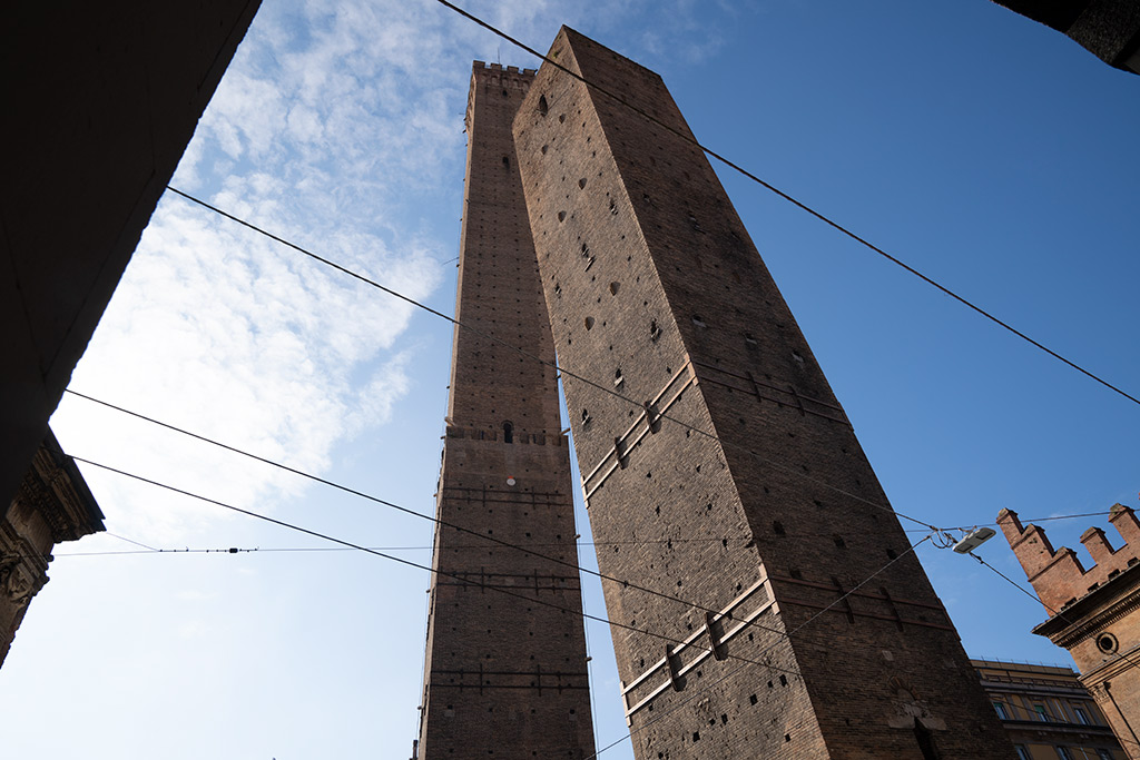 Zwei Türme aus rotem Backstein, die schief nebeneinander stehen.