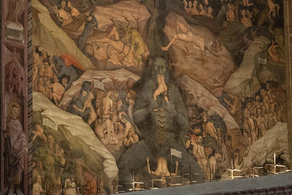 Fresko Malerei in der Capella di Magi in San Petronio in Bologna. Im Zentrum sitzt Lucifer mit zwei Händen hält er einen kleinen Menschen fest, der er sich gerade ins Maul gestopft hat. Gleichzeitig gebiert einen Menschen in die Hölle hinein.