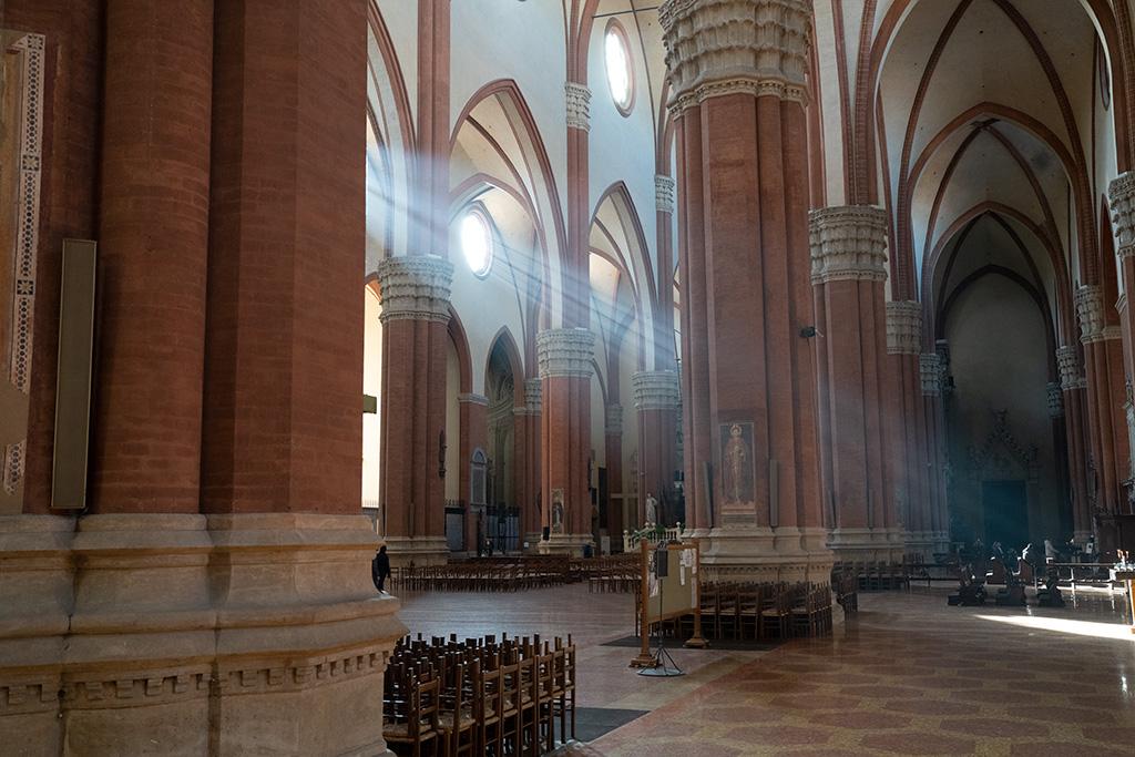 Pfeiler aus rotem Backstein tragen weiß verputzte Wände und Gewölbe. Durch große Fenster fällt Sonnenlicht in die Kirche hinein.