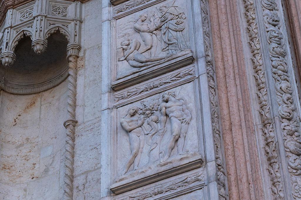 Die Portalrahmung der Kirche San Petronio in Bologna aus weißem und aus rotem Marmor. Neben gotischen Verzierungen sind Adam und Eva dargestellt.