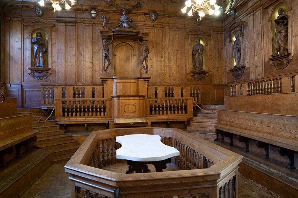 Ein holzgetäfelter Innenraum. Im Zentrum ein Tisch mit Marmorplatte umgeben von einer Balustrade. An der Rückwand eine Kanzel. Links und rechts Skulpturen an den Wänden.