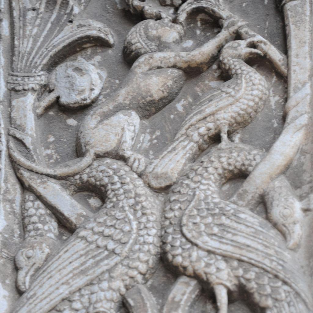 Dieses Relief vom Hauptportal der Heilige Nikolaus Kirche in Bari zeigt zwei Vögel, die mit ihren Hälsen in eine Ranke verschlugen sind. Ein Affe sitzt auf dem Hals eines der Vögel.
