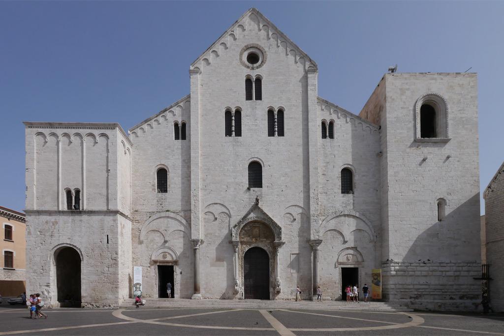 Hauptfassade der Heilige Nikolaus Kirche von Bari. Ein Hochaufragendes Mittelschiff wird von einem steilen Satteldach bedeckt. Die Dächer der Seitenschiffe sind Pultdächer. Links und rechts hat die Kirche des Heiligen Nikolaus zwei mächtige Türme. Die Kirche ist ganz aus weißem Stein erbaut.