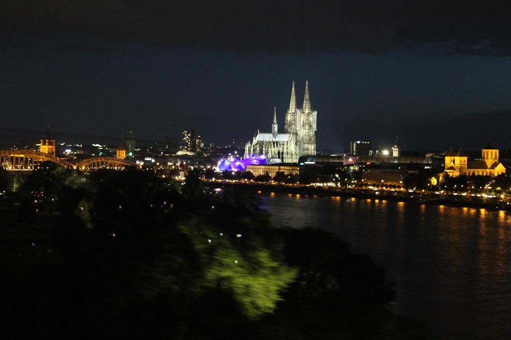 Abendliches Stadtpanorama von Köln, von der Seilbahn über den Rhein aus gesehen, aus: Reisemarkt - Fairbnb statt Airbnb: Individuelle Unterkünfte für faire Städtereisen