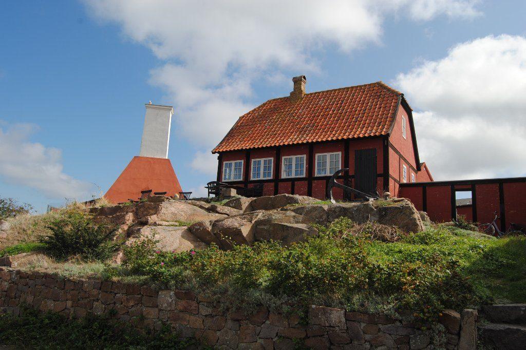 Ein rotgedecktes, rotgetünchtes Haus auf einem Steinhügel auf Bornholm. Links vom Haus ist der Schornstein einer Räucherei erkennbar.
