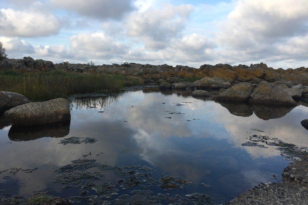 Ein spiegelglattes Gewässer umgeben von felsiger Landschaft. In dem Wasser spiegeln sich blauer Himmel und weiße Wattewolken.