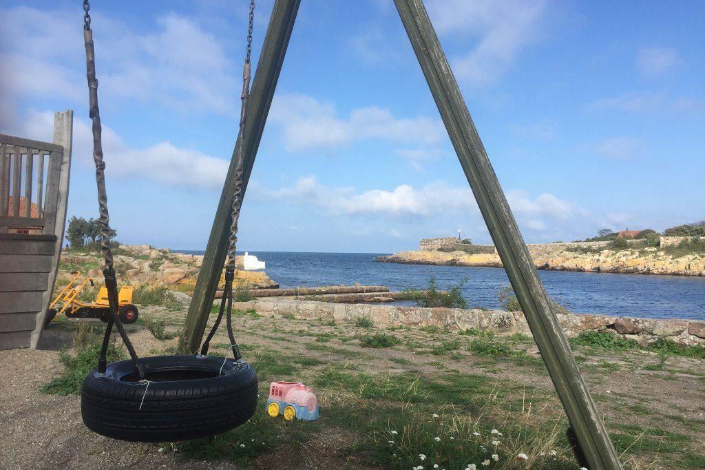 Ein Autoreifen als Sitzfläche für eine Schaukel. Daneben ein Kinderspielzeug, eine Lok in rosa und hellblau. Hinter dem Kinderspielplatz wird die Hafeneinfahrt von Christiansø sichtbar, einer kleinen Schäreninsel im Osten von Bornholm.