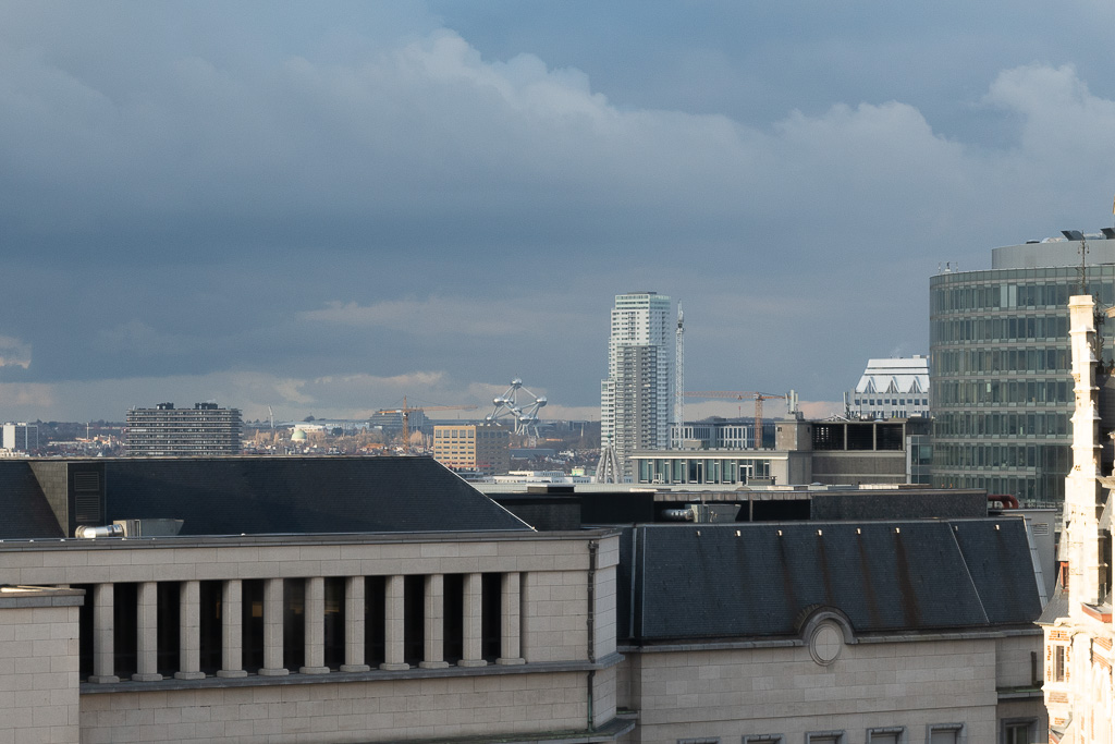 Blick über Hausdächer in Brüssel. Ganz in der Ferne sind die silber glänzenden Formen des Atomiums zu erkennen. Der Himmel ist grau.
