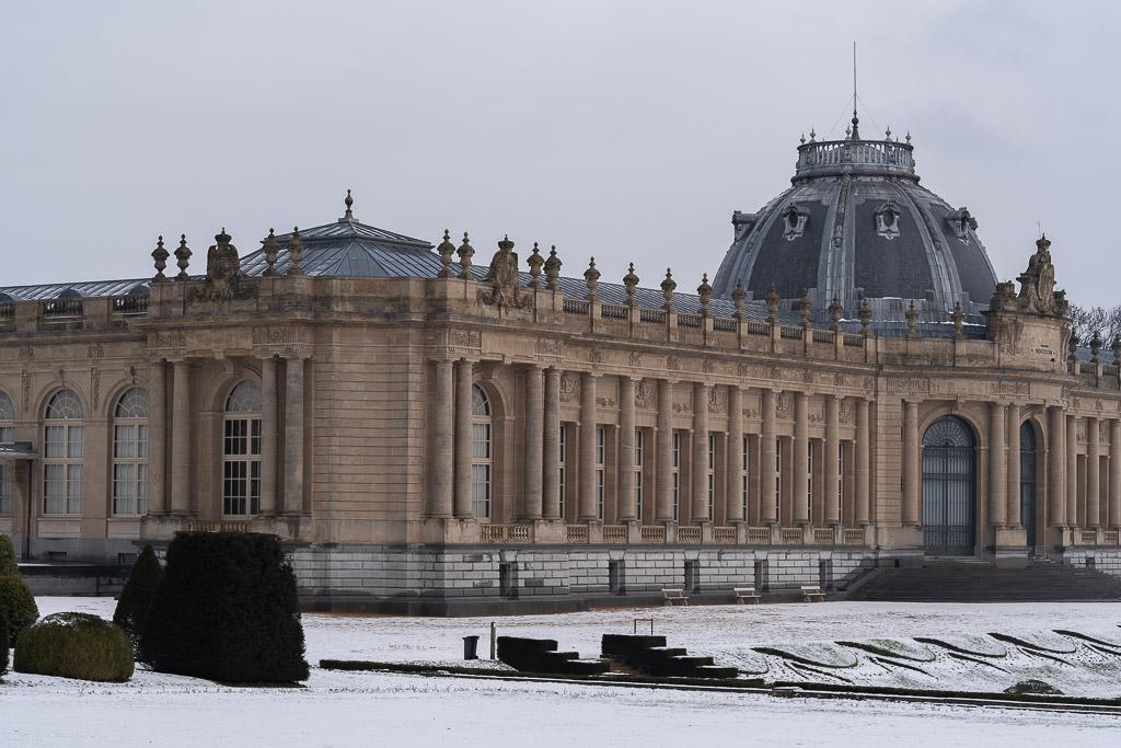 Eine von Säulen geschmückte eingeschossige Fassade in Naturstein, mit großen Fenstern. Auf der Mittelachse ist das Gebäude überkuppelt.