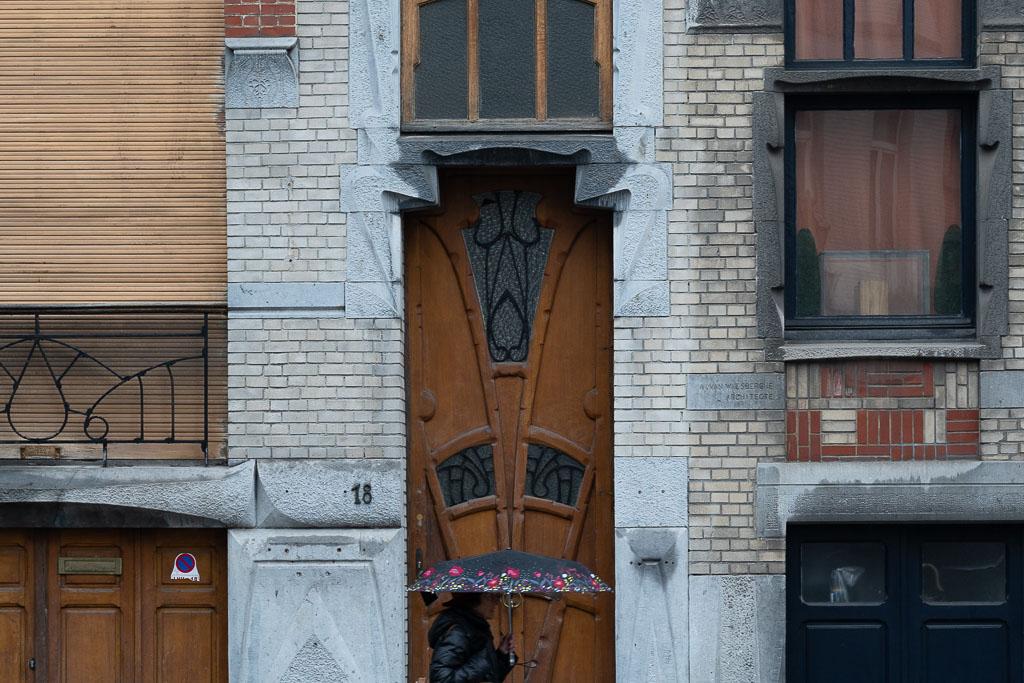 Eine reich ornamentierte Holztür gerahmt von geschwungenen Ornamenten aus Naturstein. Eine Frau mit buntem Regenschirm geht an der Tür vorbei.