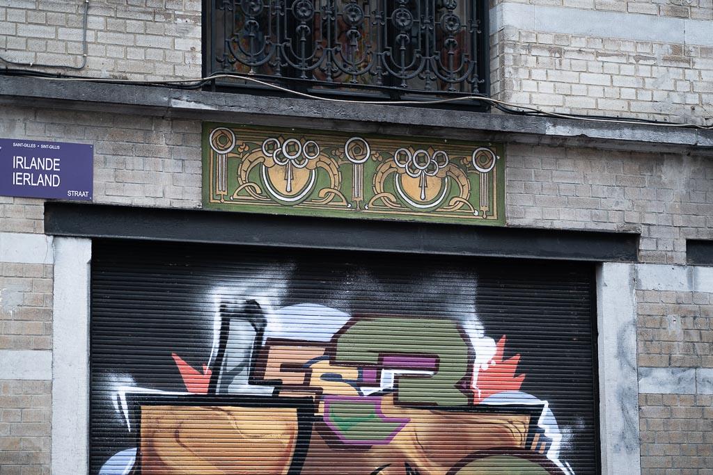 Ausschnitt einer Hausfassade aus weißem Ziegel. Balkon und Türstürze sind mit Jugendstil Ornamenten verziert. Auf herunter gelassenen Rollladen ist ein buntes Graffiti gesprüht.