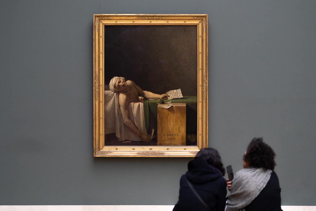 Ein Gemälde, auf dem ein toter Mann in einer Badewanne dargestellt ist, hängt in einem goldenen Rahmen vor einer grauen Wand. Davor sitzen zwei Frauen und schauen sich das Gemälde an.
