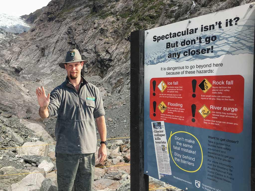 Ein Ranger steht vor dem Franz Josef Gletscher und warnt vor der weiteren Annäherung an den Gletscher.