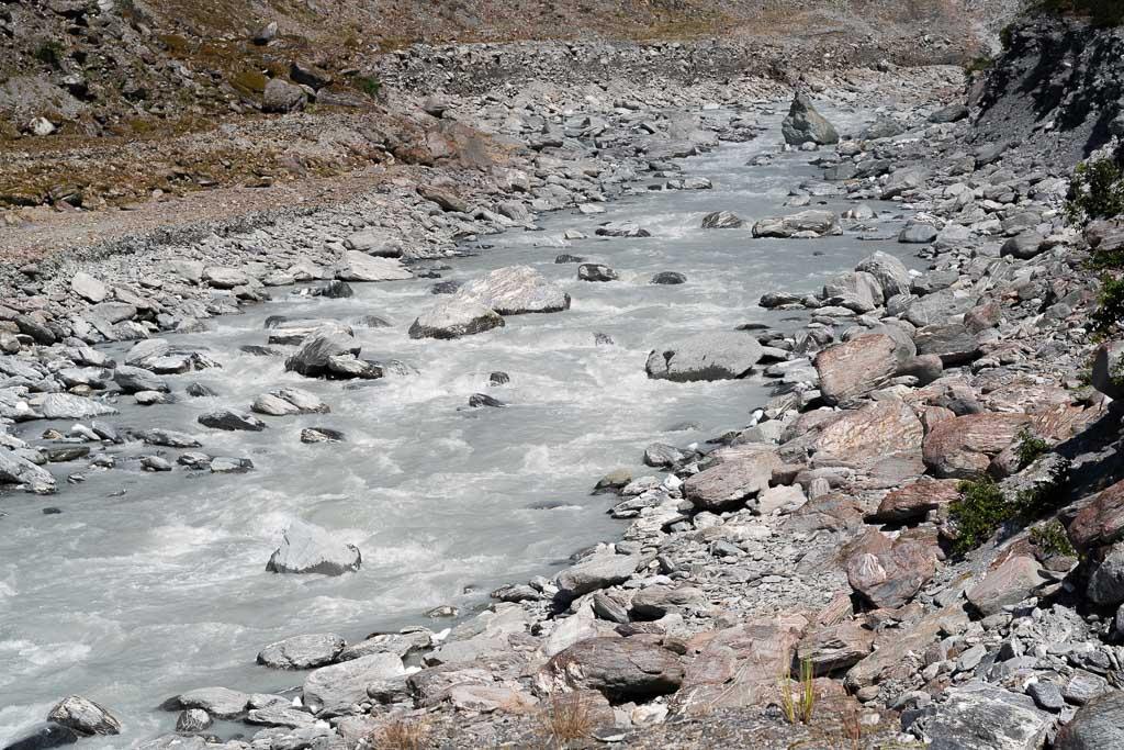 Graue Gletschermilch fließt in einem Flussbett.