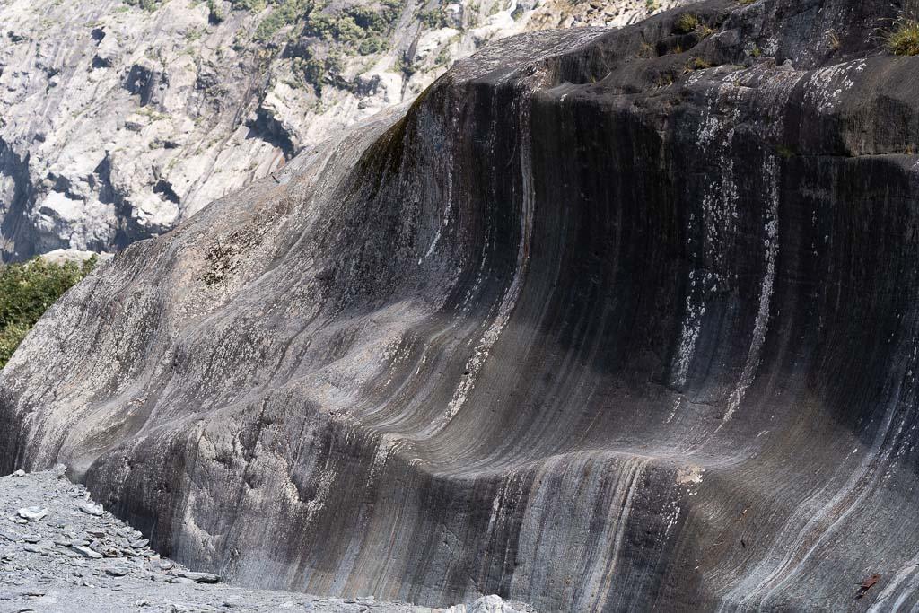 Abgeschliffene Felswand aus dunklem Granit.