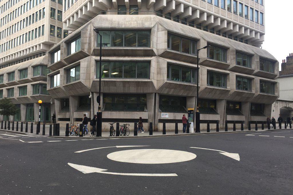 Ein Kreisverkehr mit auf den Boden gemalten Kreisen. Im Hintergrund das Justizministerium im Architekturstil des Brutalismus.