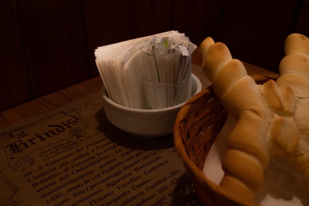 Ein Brotkorb auf einem Tisch. Dahinter ist ein Becher mit Zahnstochern aufgestellt.