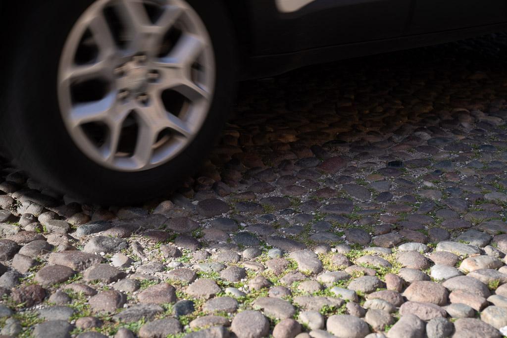 Straßenpflaster in Ferrara aus Flusskieseln. Ein Auto fährt darüber.