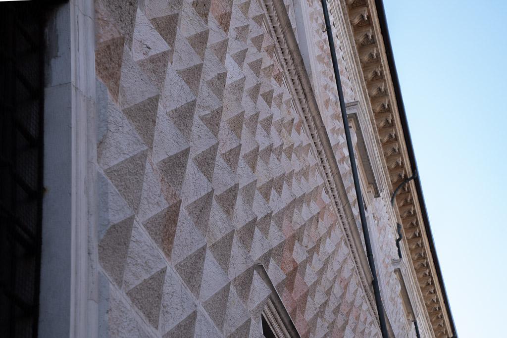 Die Fassade des Palazzo dei Diamanti wird von weißem Kalkstein verziert.
