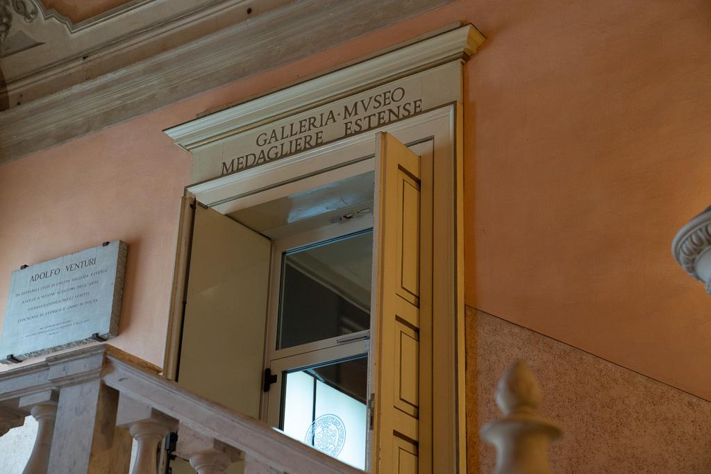 Eine alte, weiß gestrichene Flügeltür. Über dem Türsturz befindet sich eine Inschrift: Galleria Estense Modena.