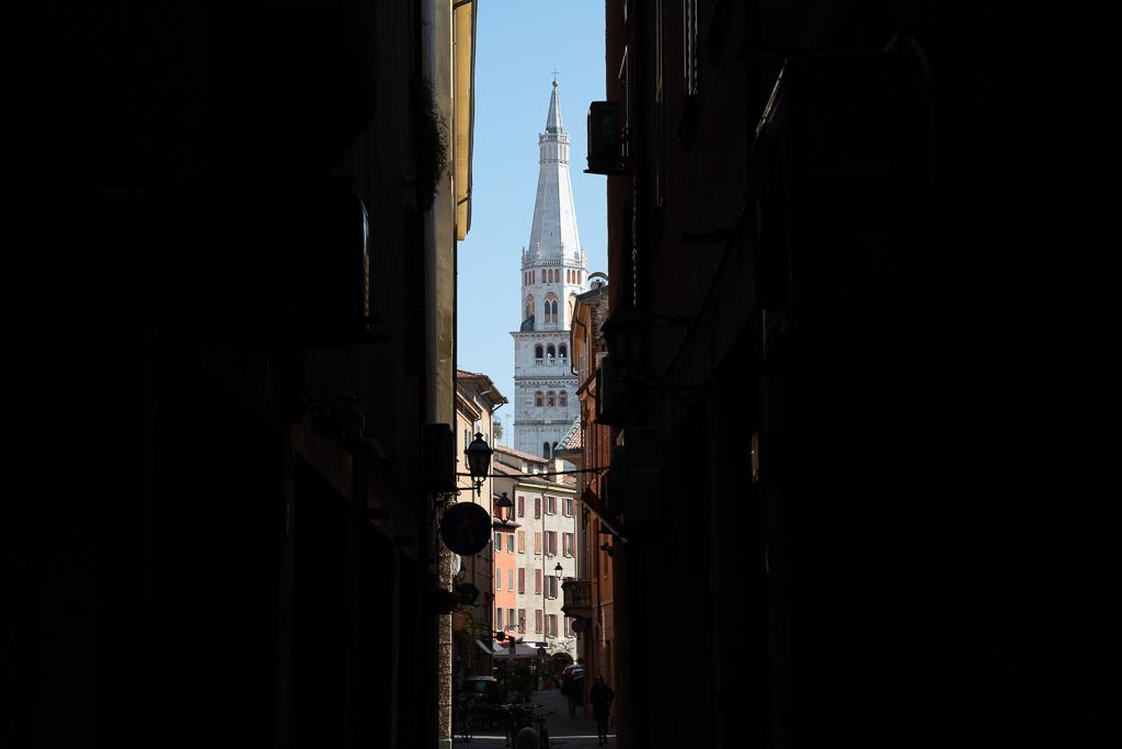 Blick durch eine dunkle Gasse auf einen weißen Kirchturm, den Torre Ghirlandina.