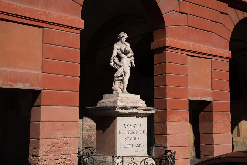 Eine Bogenarkade in Modena. Die Bögen sind rot verputzt. In einem Bogen ist auf einem Sockel die Skulptur eines Mannes mit einem kleinen Kind auf dem Arm aufgestellt.