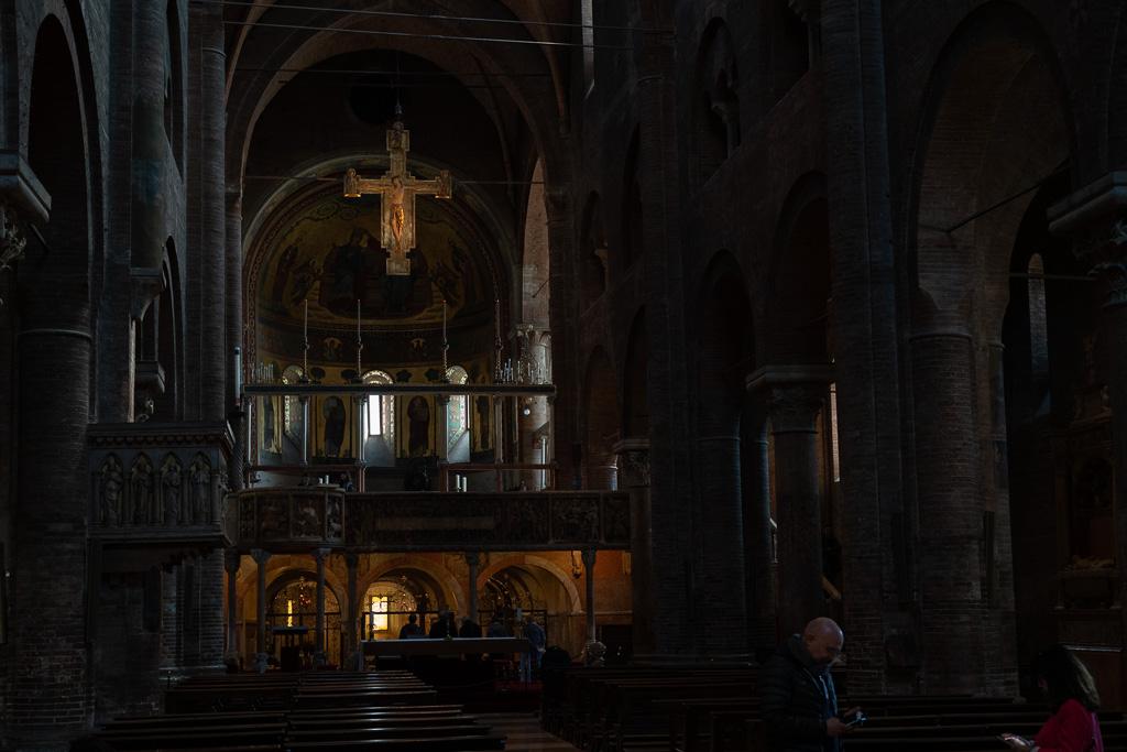 Innenraums der Kathedrale von Modena. In der Mitte des Bildes leuchtet ein goldenes Kreuz.