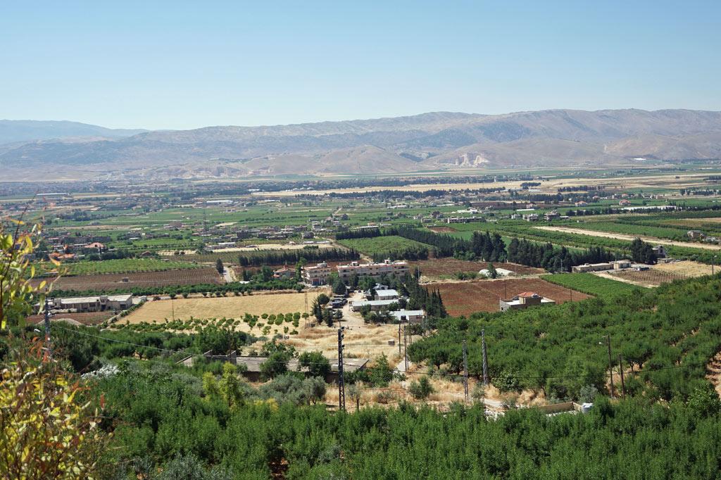 Blick über die Bekaa-Ebene, Kornkammer des Libanon. Bahnhof und Eisenbahn Fabrik von Rayak befinden sich in der linken Bildmitte, gleich hinter der hellen Fläche des benachbarten Militärflughafens. Jenseits der Berge im Hintergrund liegt Syrien.