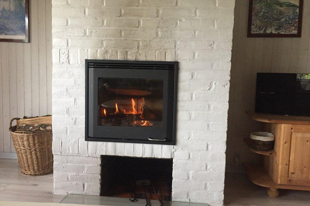 Ein brennender Kamin, außen weiß getüncht mit leichten Rauchspuren, gesäumt von einem Korb mit Holzscheiten und einem dänischen Wohnmöbel aus Kiefernholz.