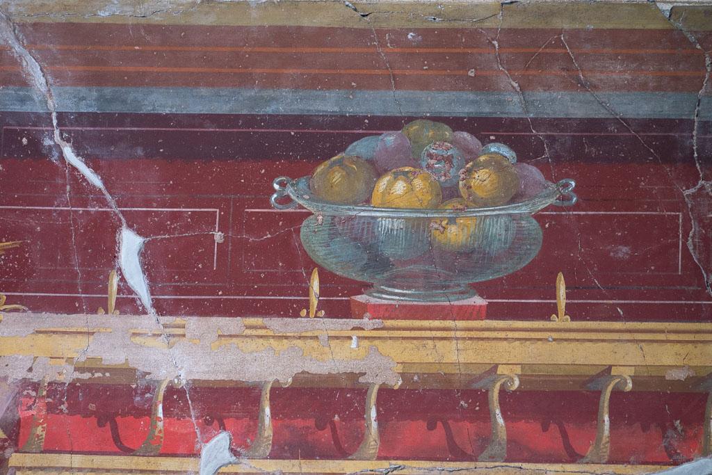 Ein Wandgemälde mit rotem Hintergrund. Auf einem Gesims steht eine Glasschale, die mit Früchten, Quitten, Pflaumen und Feigen gefüllt sind.