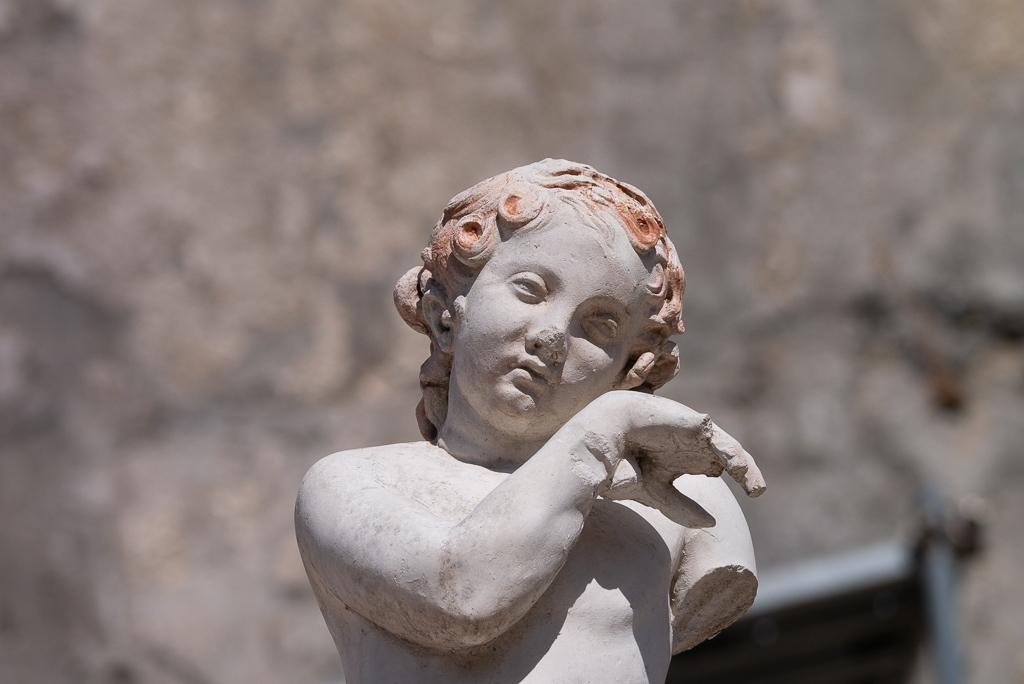 Die Skulptur eines Knabens, der seine linke Hand an die Wange führt, als ob er Tränen trocknen wollte. Sein Kopf ist leicht nach rechts geneigt. Die Haare sind gelockt und rot angemalt.