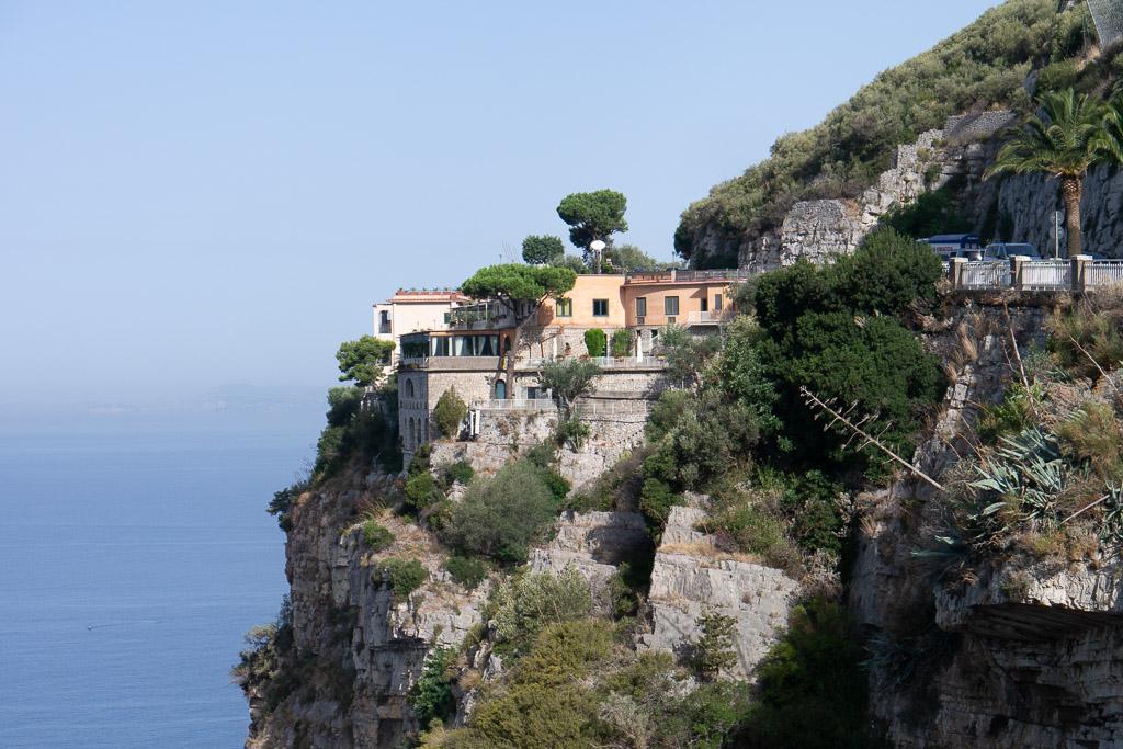 Steilküste am Golf von Neapel mit Pinien und Palmen bewachsen.
