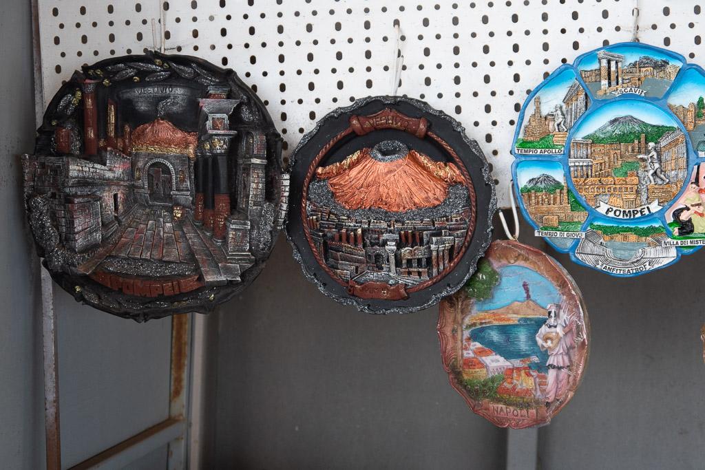 Teller mit dem Motiv des Vesuv und des Golf von Neapel. Sie sind mit Reliefs und bunten Farben geschmückt und zeigen den Vulkan hinter der Stadtkulisse von Pompeji oder den Sehenswürdigkeiten am Golf.