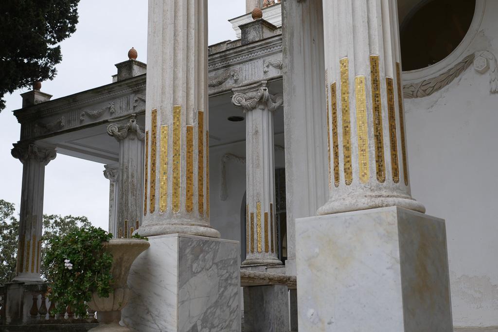 Nahaufnahme von weißen Säulen auf hohen Sockeln. Die Säulen gehören zur Vorhalle der Villa Lysis auf Capri, einer der schönsten Orte am Golf von Neapel.