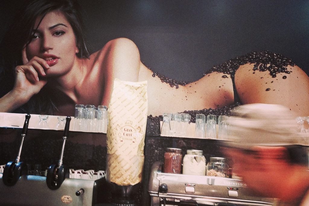 Bar in Neapel, auf einer Fototapete liegt ein Frau und schaut in die Kamera.