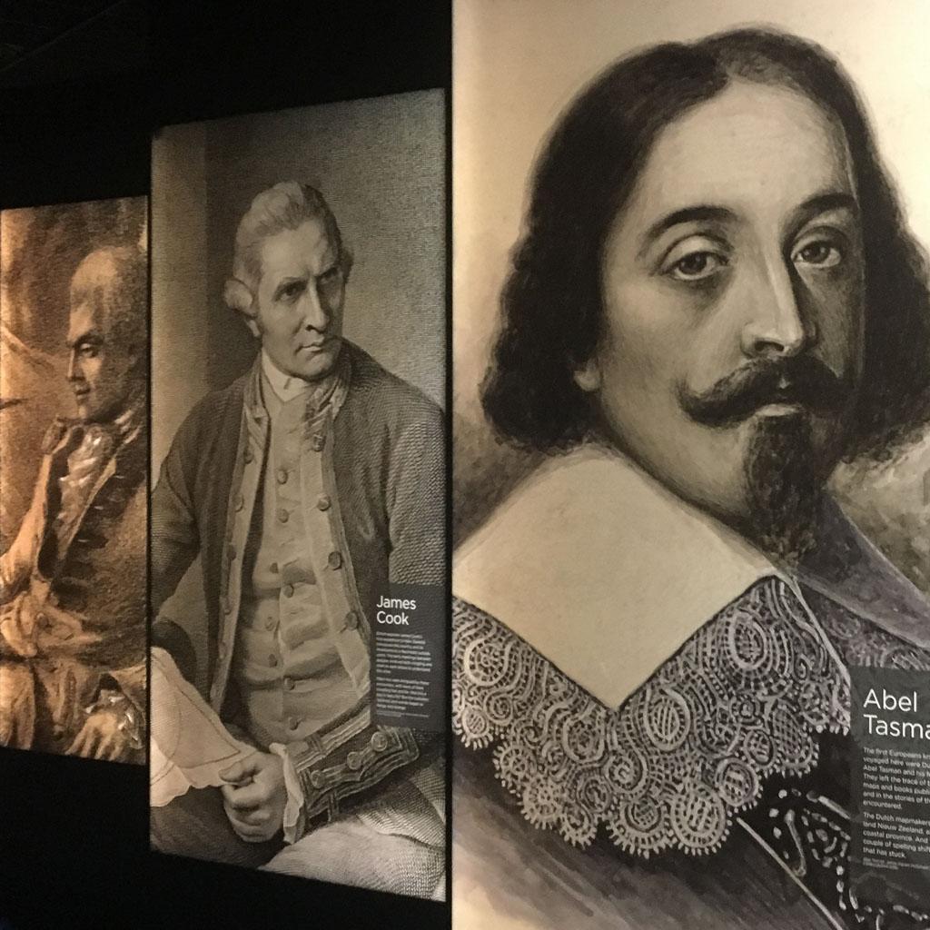 Das Bild aus dem Museum der Treaty Grounds von Waitangi zeigt 3 Kuperstiche auf denen Männer mit langen Haaren und Perücken dargestellt sind. Sie sind angezogen in der Mode des 17. und 18. Jahrhunderts. Sie schauen sehr streng.