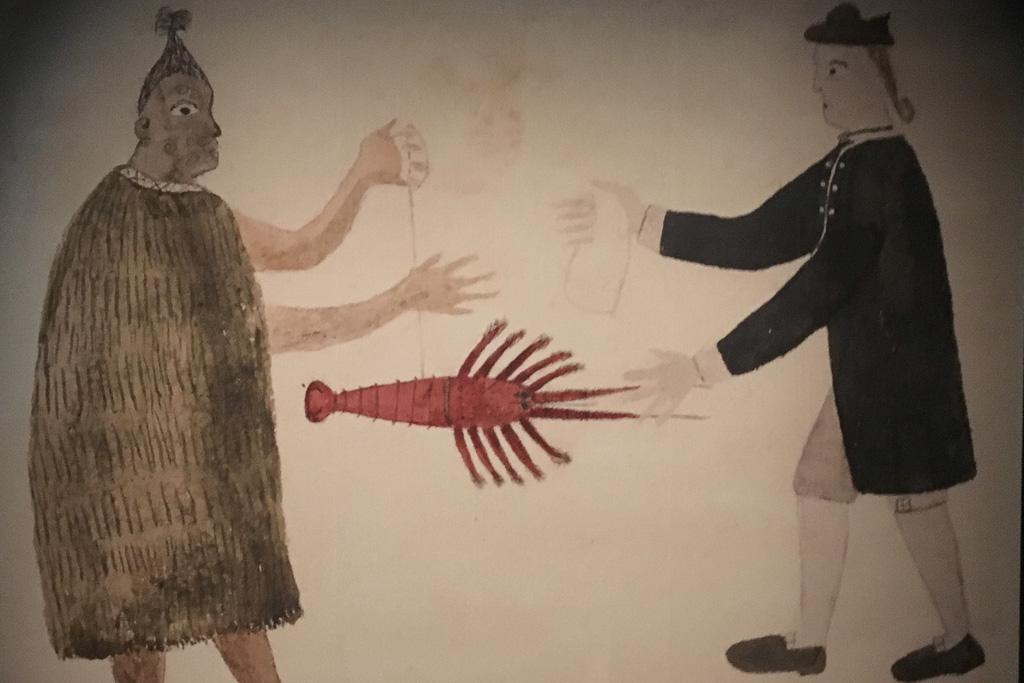 In diesem Bild aus dem Museum in Waitangi steht rechts ein Mann, in einen braunen Umhang gehüllt. Er reicht einen roten Hummer an einem Mann auf der linken Seite, der einen schwarzen Anzug und eine Perücke trägt.