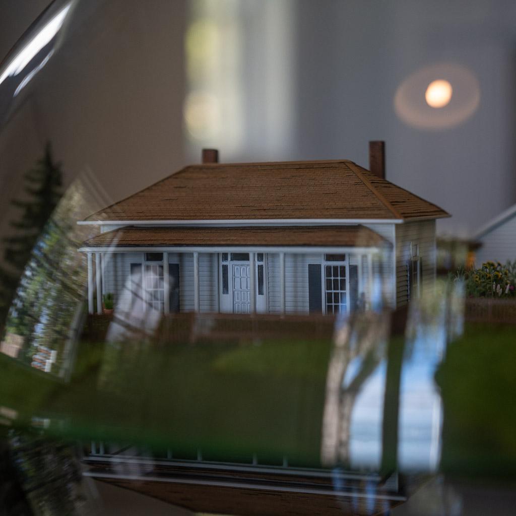 Ein kleines weißes Holzhaus mit einem roten Dach und zwei Schornsteinen unter einer Glashaube aus dem Museum in Waitangi.