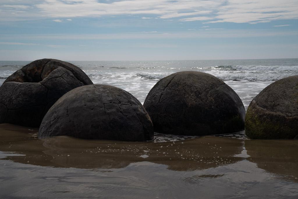 Das Bild zeigt große runde Steine, die Moeraki Boulders, die im feuchten Sand stecken. Im Hintergrund rollt eine große Welle Richtung Küste. Der Himmel ist blau und etwas Wolken verhangen.