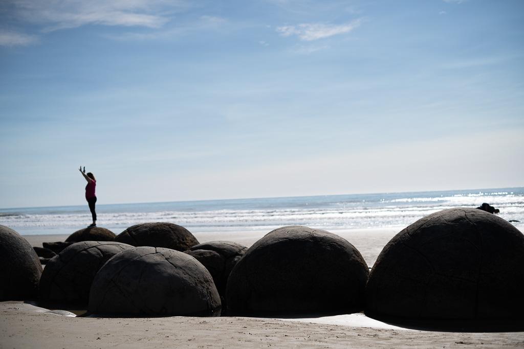 Das Bild zeigt einen weiten Horizont mit blauem Himmel. im Vordergrund der Sandstrand des Koekohe Beach. Auf runden Steinen, den Moeraki Boulders, steht eine Frau mit erhobenen Armen.