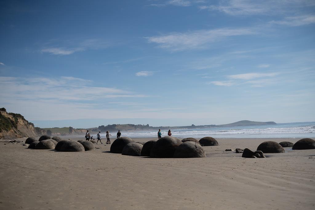 Das Bild zeigt einen Sandstrand am Pazifik. Vorne Sand, dahinter das Meer und eine hügelige Landzunge. Über die Hälfte des Bildes nimmt der blaue Himmel ein.