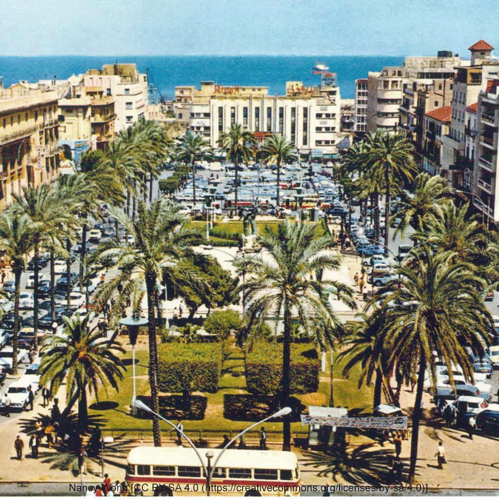 Historisches Foto des Märtyrerplatzes aus den 1970er Jahren. Das Bild zeigt Palmen und Grünanlagen, außerdem einen Parkplatz und unregelmäßige, aber abwechslungsreiche Bebauung und das Meer im Hintergrund.